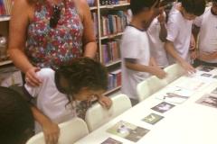 Crianças da Escola ANNE SULLIVAN – SP vendo fotos do processo de desenvolvimento do livro da Missy em uma mesa