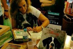 Izabella autografando livros em sua mesa no lançamento