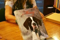 Livro sobre a mesa e ao fundo Izabella dando autógrafos