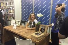 Izabella em sua mesa dando atenção aos leitores a Bienal de Belo Horizonte no Stand da Leitura